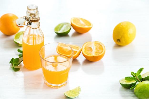 Vaso y botella de licor de naranja y naranjas crudas
