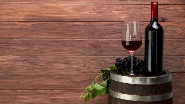 Vaso y botella de vino encima de un barril
