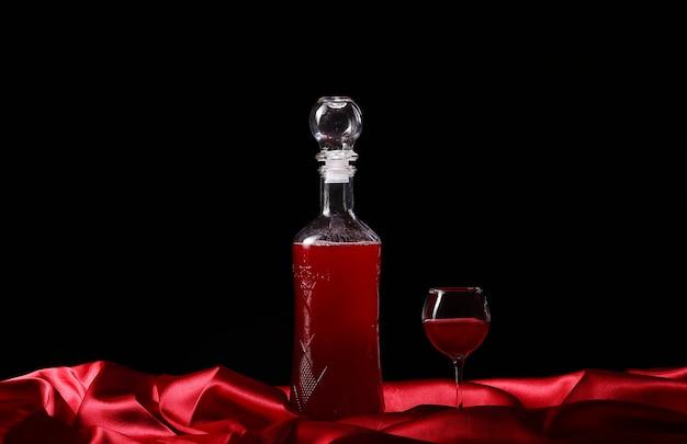 Vaso y botella de vino sobre un fondo oscuro de seda