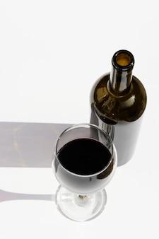 Vaso y botella de vino con sombras oscuras aisladas en blanco