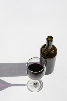 Vaso y botella de vino con sombras oscuras aislado en un blanco