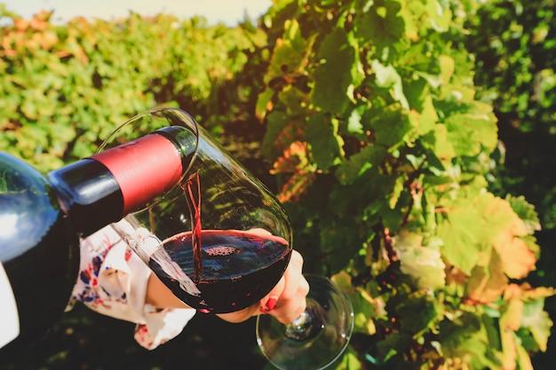 Vaso y botella de vino tinto en enfoque selectivo en copa de vino vertiendo vino tinto