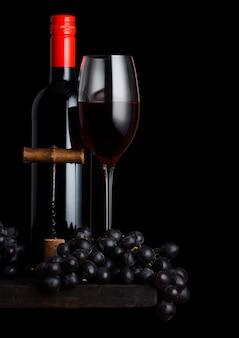 Vaso y botella de vino tinto con uvas oscuras y abridor de sacacorchos vintage y corcho sobre tabla de madera sobre negro