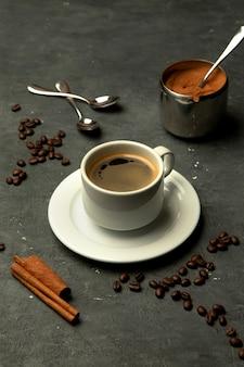 Vaso de café americano en fondo gris decorado con granos de café.