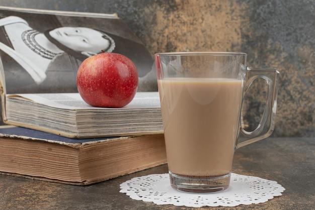 Un vaso de café caliente con una manzana roja y libros sobre la superficie de mármol.