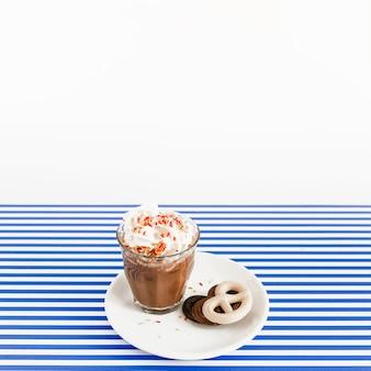 Vaso de café con crema batida y chocolates de pretzel en un plato sobre fondo de rayas blancas y azules