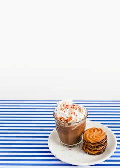 Vaso de café con crema batida y pila de galletas en un plato sobre fondo de rayas