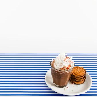 Vaso de café con crema batida y pila de galletas en un plato sobre fondo