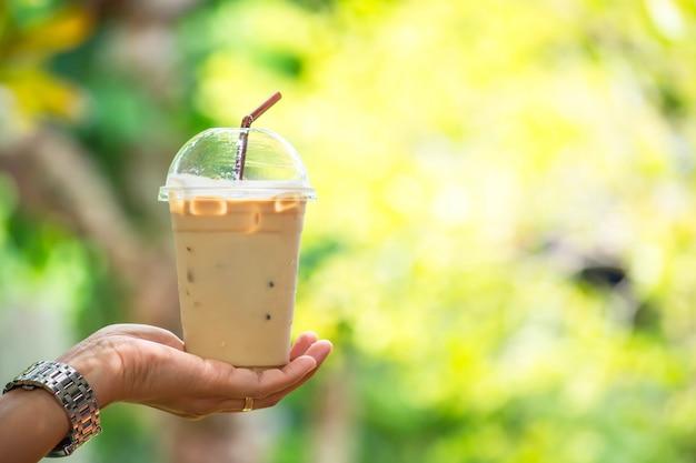 Vaso de café expreso frío en la mano, árbol de vistas borrosas.