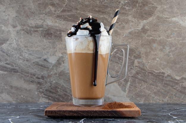 Vaso de café frío espumoso con crema batida y chocolate sobre placa de madera.