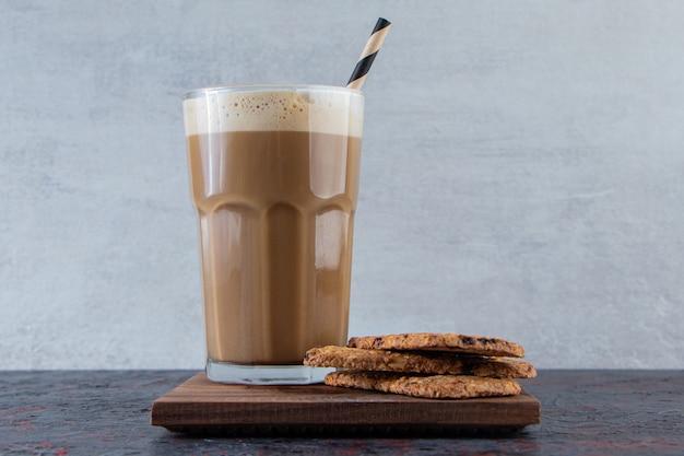 Vaso de café frío espumoso con galletas en placa de madera.