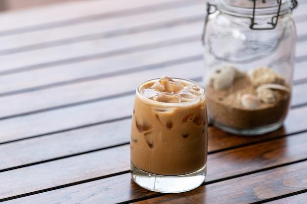 Vaso de café helado con arena en lámpara de botella sobre mesa de madera.