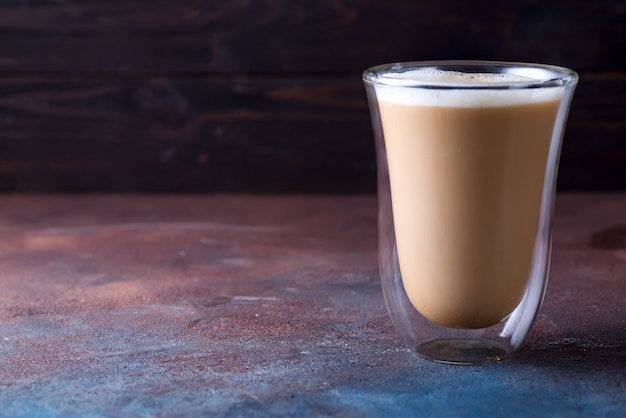 Vaso de café con leche en la mesa de piedra oscura