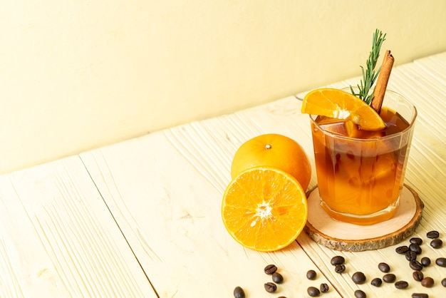 Un vaso de café negro americano helado y una capa de jugo de naranja y limón decorado con romero y canela.