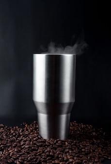 Vaso de café negro caliente con platillo de vidrio en un montón de semillas de café. café oscuro caliente y vapor. de cerca. vista superior.