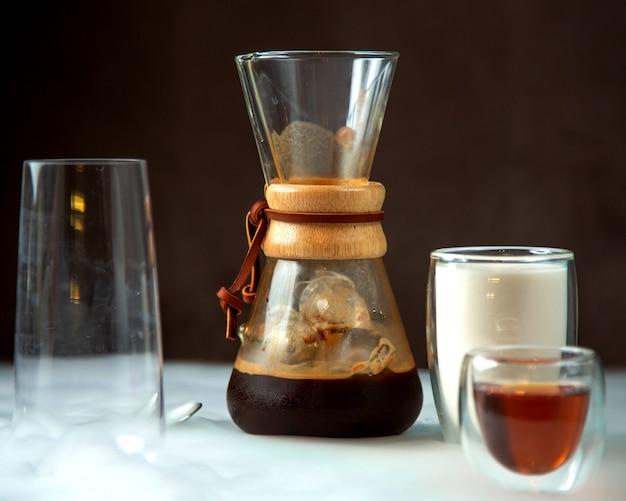 Un vaso de café en un vaso con forma única servido con leche y jarabe