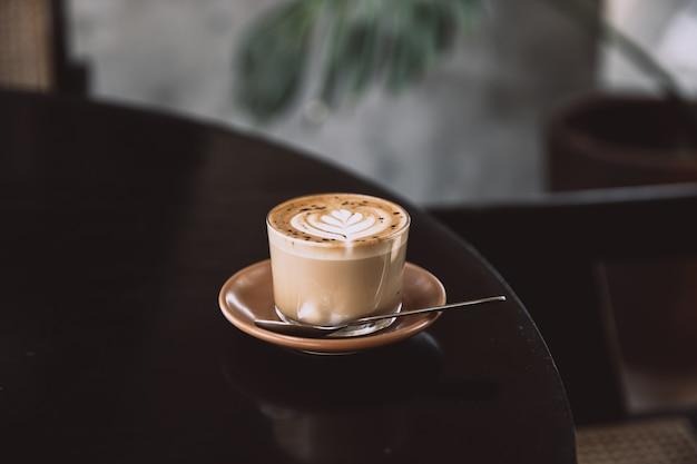 Vaso de capuchino con arte latte en platillo y con cuchara sobre la mesa negra. bebida de desayuno
