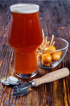 Un vaso de cerveza y aperitivos en una mesa de madera.