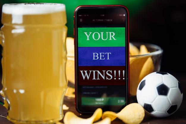 Vaso de cerveza y aplicación móvil con concepto de juego de apuestas ganadoras