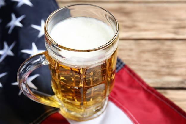 Vaso de cerveza y bandera americana en la mesa