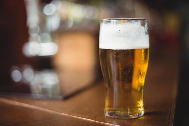 Vaso de cerveza en barra de bar