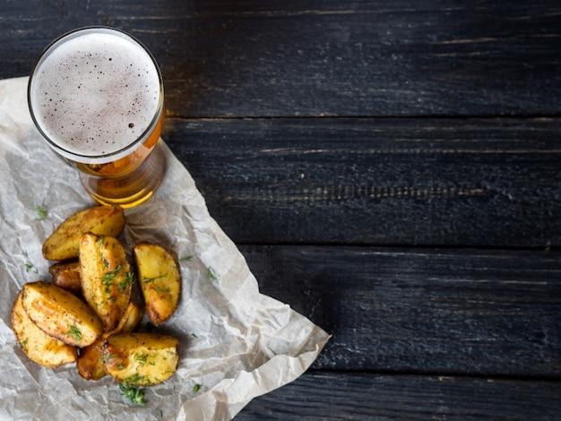 Vaso de cerveza y bocadillos en forma de papas crujientes con eneldo en una mesa de madera oscura vista desde arriba con copyspace