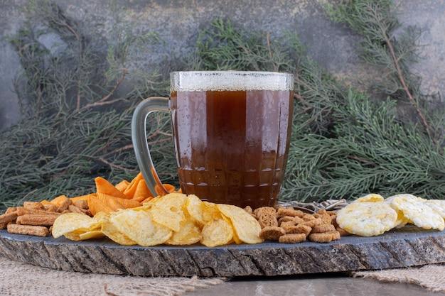 Vaso de cerveza y bocadillos en pieza de madera