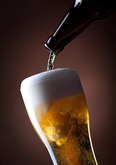 Vaso de cerveza y botella en un marrón