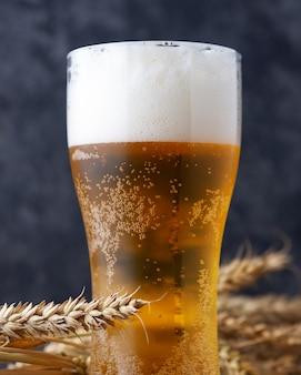 Un vaso de cerveza contra una pared oscura.