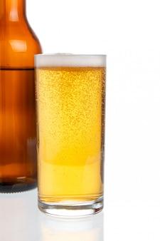 Vaso con cerveza d botella de cerveza sobre fondo blanco.