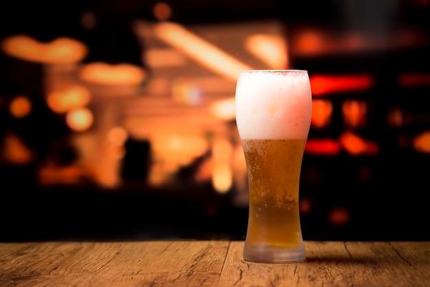 Vaso de cerveza delante de fondo borroso
