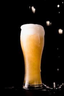Vaso de cerveza delante de fondo negro