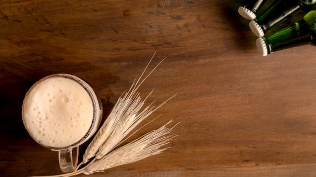 Vaso de cerveza con espiga de trigo y botellas verdes en mesa de madera