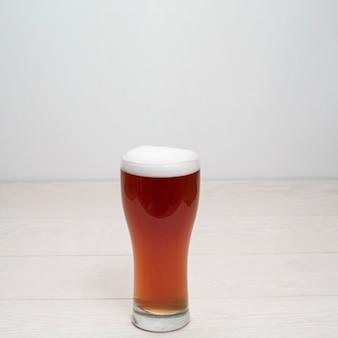 Vaso de cerveza con espuma en la mesa