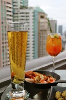 Vaso de cerveza fría con cóctel de sangría borrosa y tapas en la terraza del bar de la azotea