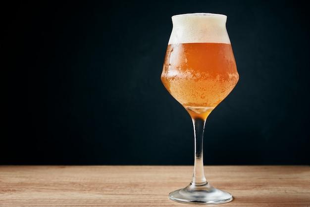 Vaso de cerveza fría con espuma en la oscuridad