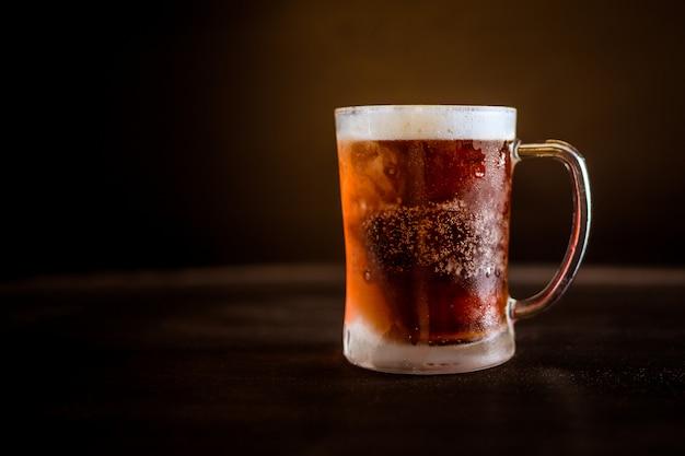 Un vaso de cerveza fría con fondo marrón oscuro