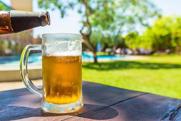 Vaso de cerveza fría en la mesa del café al aire libre