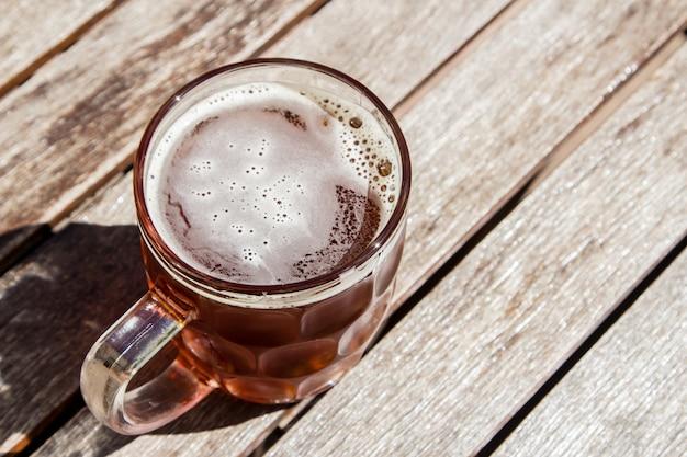 Vaso de cerveza fría sobre una superficie de madera en un día caluroso y soleado