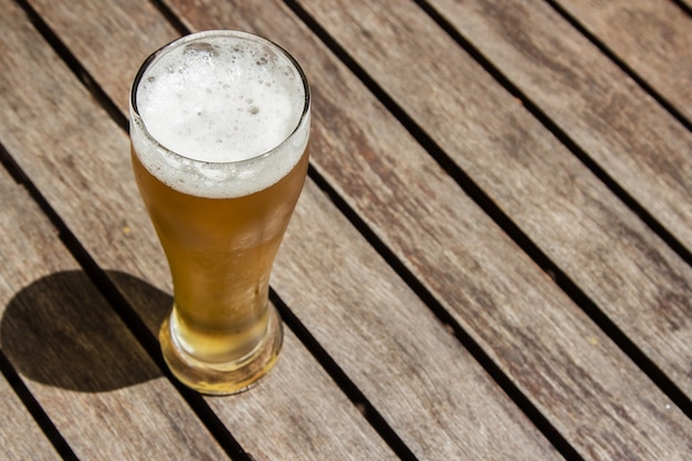 Vaso de cerveza fría sobre una superficie de madera en un día soleado