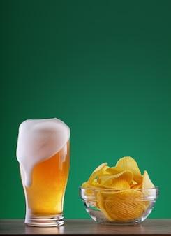 Vaso de cerveza ligera con espuma de goteo y plato de papas fritas