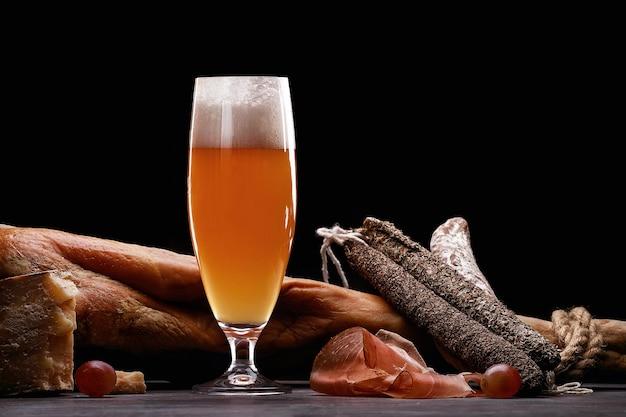 Un vaso de cerveza ligera de espuma, pierna, jamón de parma, variedades caras de embutidos y queso con moho. sobre fondo negro. lugar para logo.