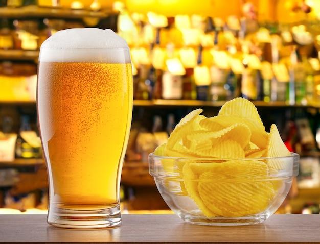 Vaso de cerveza ligera y papas fritas en barra de bar en pub