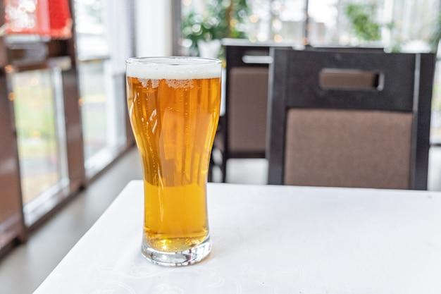 Vaso de cerveza ligera sobre una mesa en un bar.