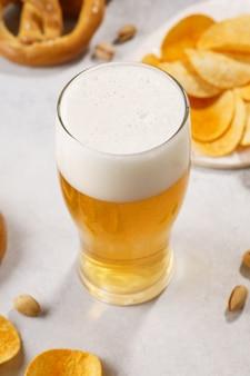 Vaso de cerveza ligera y variedad de bocadillos: galletas saladas, papas fritas y pistachos.