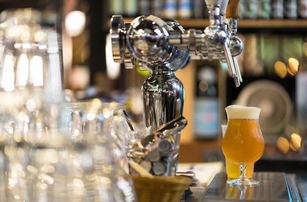 Vaso de cerveza light, que sirve cerveza fresca en barra de bar.