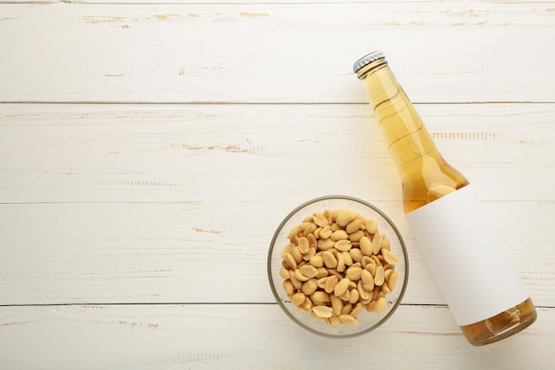 Vaso de cerveza con maní sobre fondo blanco de madera. vista superior