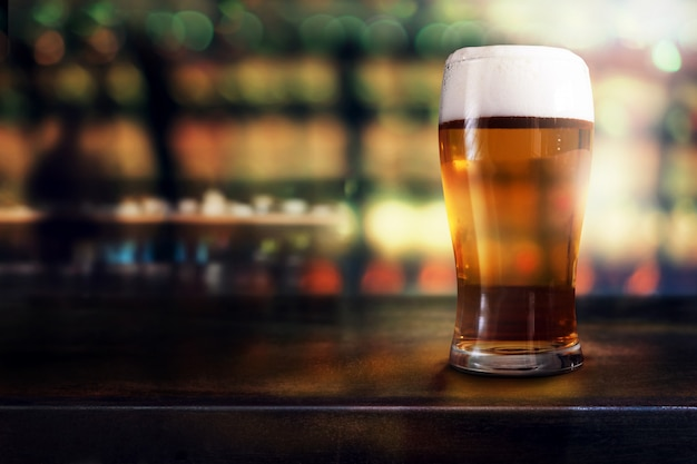 Vaso de cerveza en la mesa en el bar o restaurante. vista lateral. escena nocturna