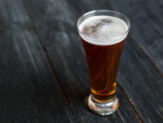 Un vaso de cerveza en una mesa de madera oscura.