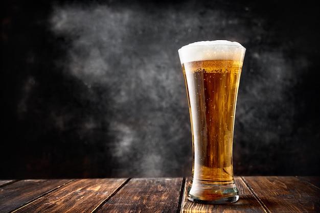 Un vaso de cerveza en la mesa de madera.